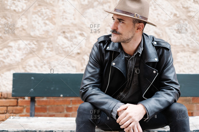Serious male with mustache wearing hat and leather jacket relaxing on bench and looking away near stone brick wall