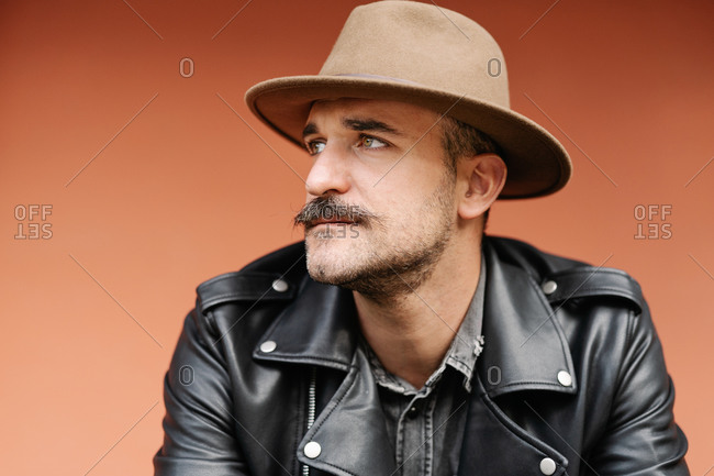 Trendy thoughtful male in hat and leather jacket on beige background looking away