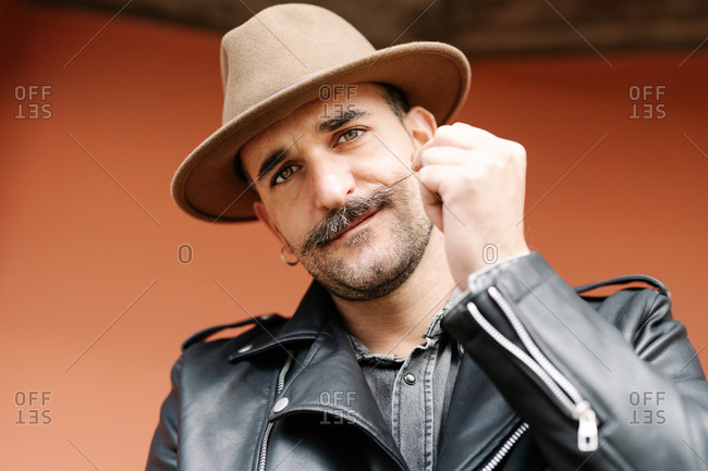 Mature male in leather jacket curling mustache while looking at camera standing on orange background