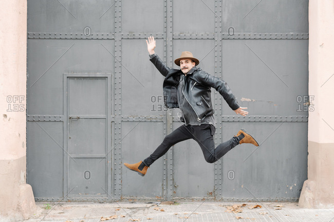 Full body of stylish thoughtful male with mustache in hat leaping and looking at camera near building with metal door and wall