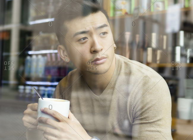 Asian male relaxing in armchair in cozy coffee shop and enjoying hot beverage while looking away