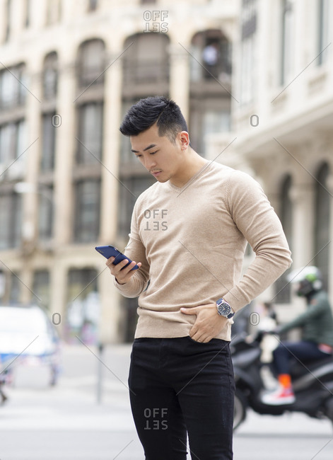 Masculine Asian male standing with hand in pocket and browsing mobile phone in city while looking down