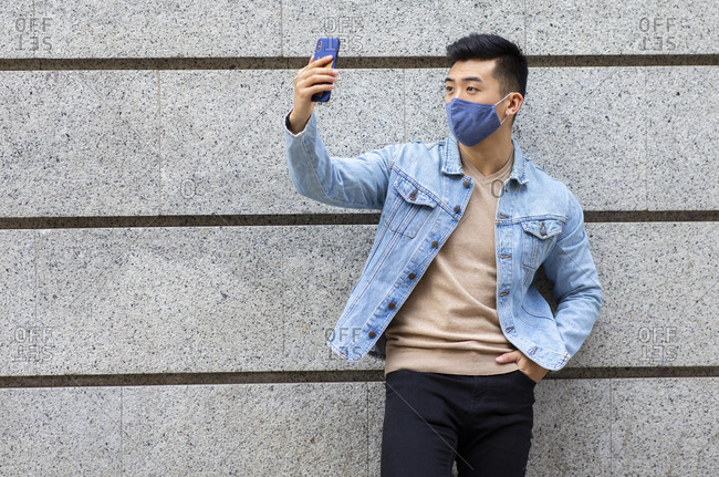 Asian male wearing medical protective mask standing near building and taking selfie on smartphone during coronavirus epidemic in city