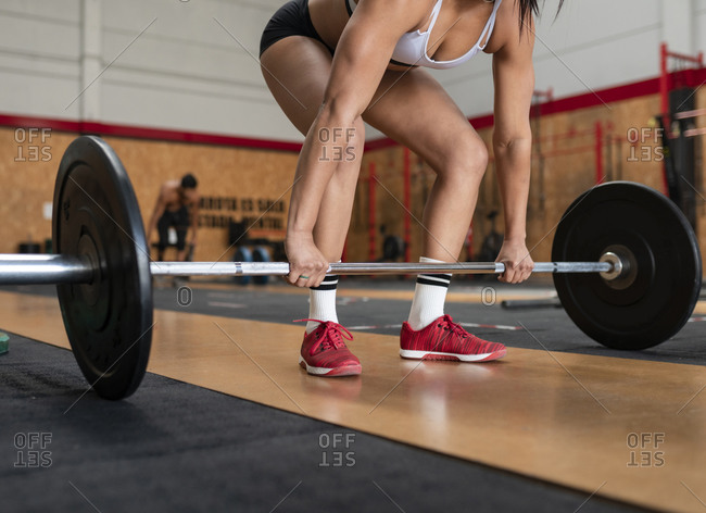 Crop unrecognizable strong female in sportswear doing deadlift exercise with heavy barbell in sports center