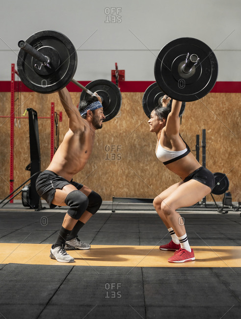 Side view of muscular sportsman and sportswoman lifting heavy barbells and making effort while looking at each other and doing exercises during weightlifting training