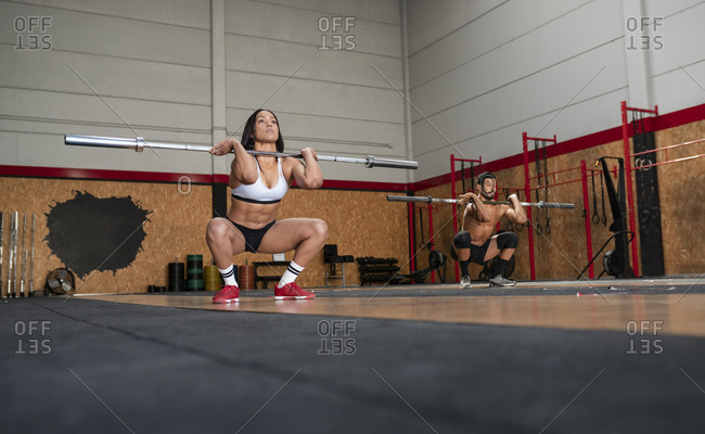 Ground level of muscular sportsman and sportswoman doing squats with barbells while training actively in gym together and looking away