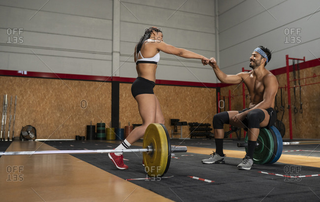 Side view of muscular sportswoman and sportsman cheerfully bumping fists before weightlifting training in gym