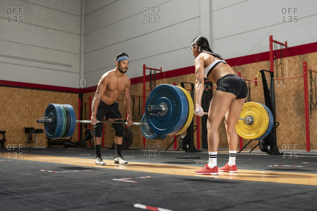 Muscular sportsman and sportswoman lifting heavy barbells and making effort while looking at each other and doing exercises during weightlifting training