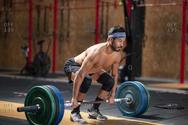 Concentrated male athlete lifting heavy barbell during weightlifting workout in gym while looking away