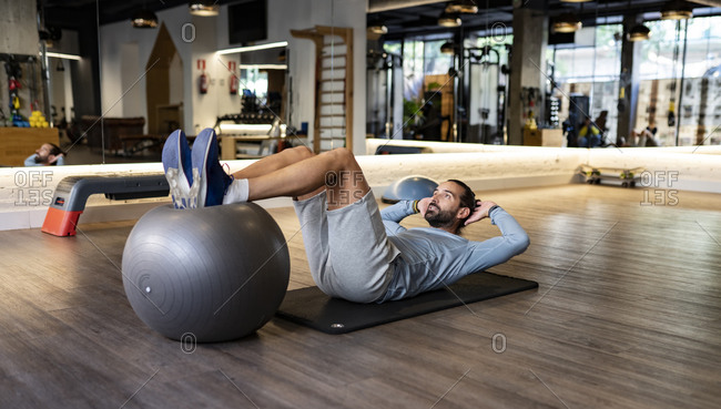 Bearded adult male athlete holding legs on fit ball and doing abdominal crunches on mat during fitness training in gym