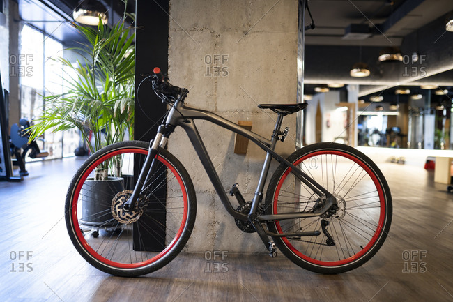Modern black bicycle parked near concrete pillar inside contemporary illuminated gym during workout