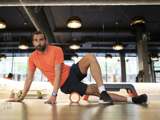 Bearded adult sportsman doing exercise with roller against mirror during fitness training in contemporary gym