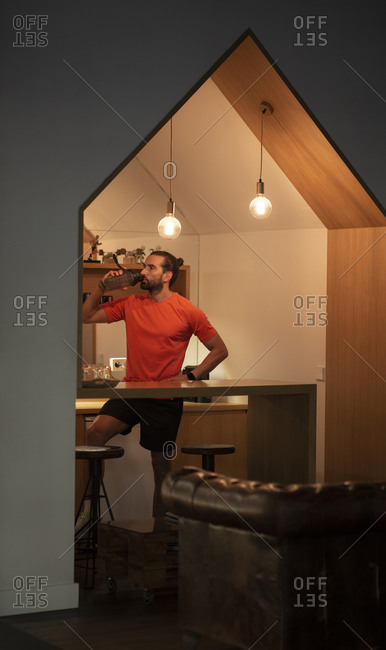 Confident sportsman with hand on waist standing in kitchen and drinking water after fitness workout in gym