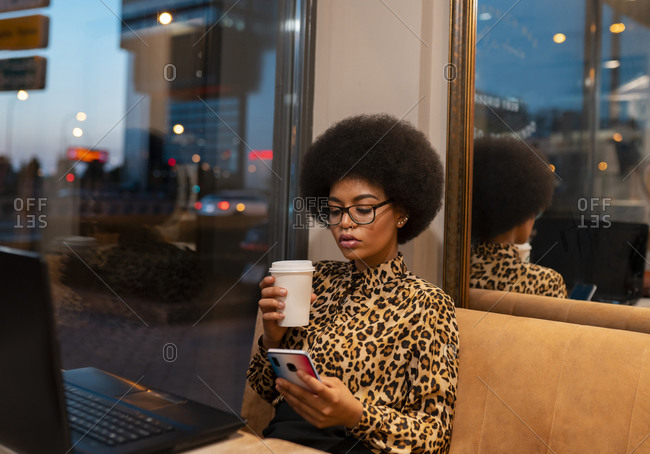 Serious African American female with afro hair scrolling cellphone while working remotely at table with laptop in cafe sitting near glass window enjoying hot beverage on take away cup