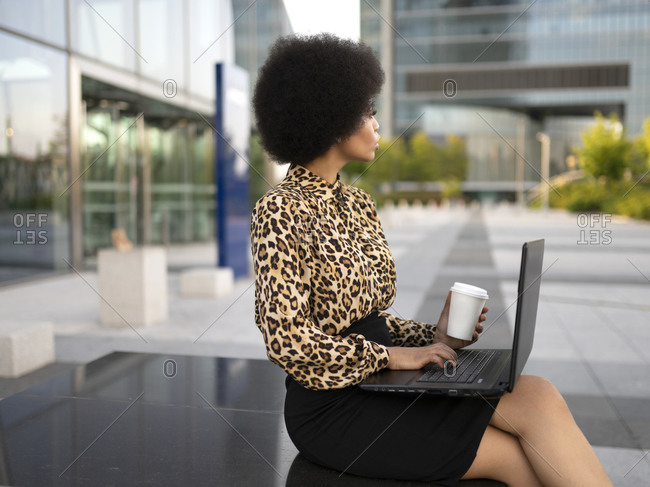 Side view of busy African American female manager sitting on bench with computer and cup of drink and typing text while working remotely near glass building