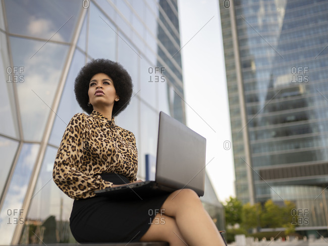 From below busy African American female with afro sitting on bench with computer typing text while working remotely near glass building