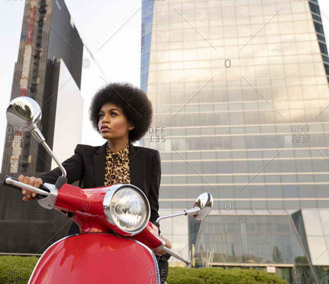 From below of confident African American female with motorcycle wearing black classic outfit looking away