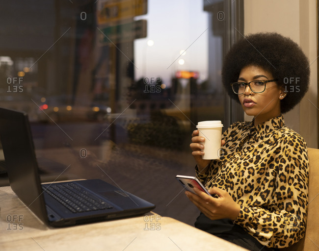 Serious African American female with afro hair scrolling cellphone while working remotely at table with laptop in cafe sitting near glass window enjoying hot beverage on take away cup looking at camera