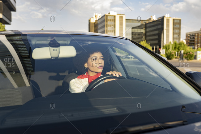 Through window of thoughtful focused young African American female driving automobile on the road