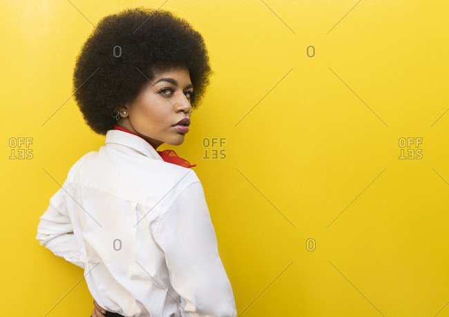 back view of confident African American female in elegant formal outfit standing looking over the shoulder to the camera against yellow background