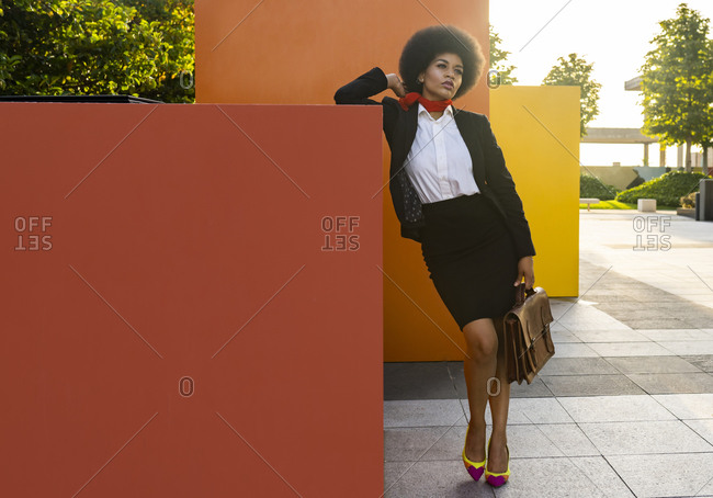 Full body of elegant African American businesswoman in classy suit leaning on red cube and thoughtfully looking away