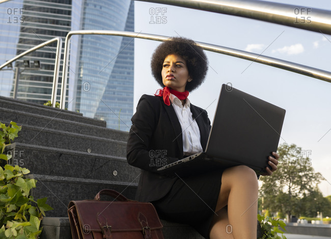 From below serious African American entrepreneur with afro hair working on laptop sitting on stairs looking away