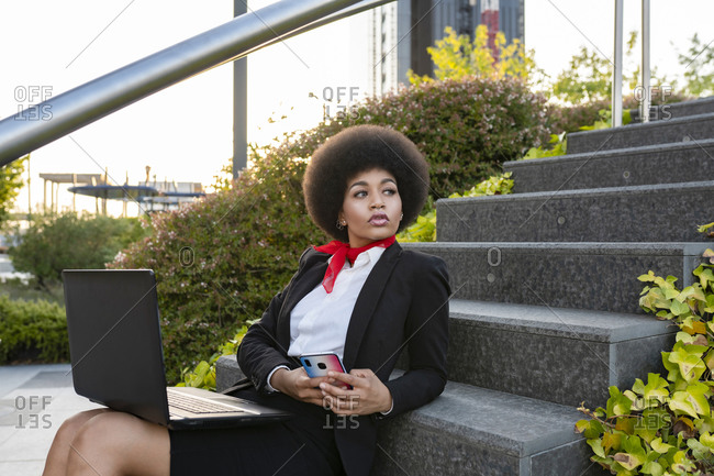 Serious African American entrepreneur with afro hair working on laptop sitting on stairs looking away