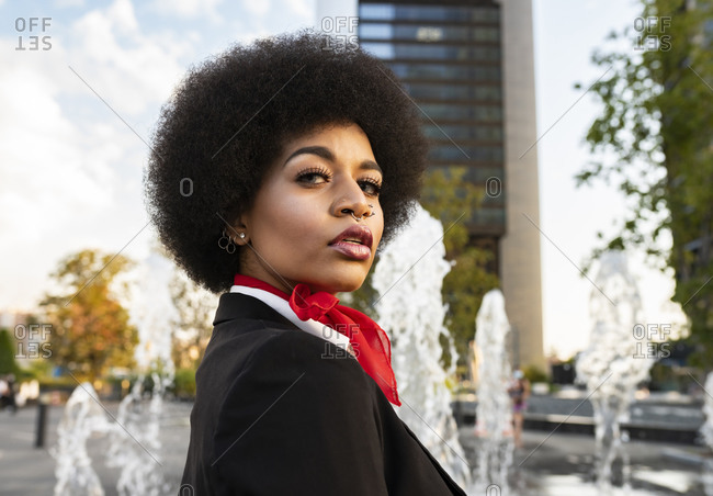 Low angle side view of confident African American female in formal jacket with curly hair and piercing thoughtfully looking at camera