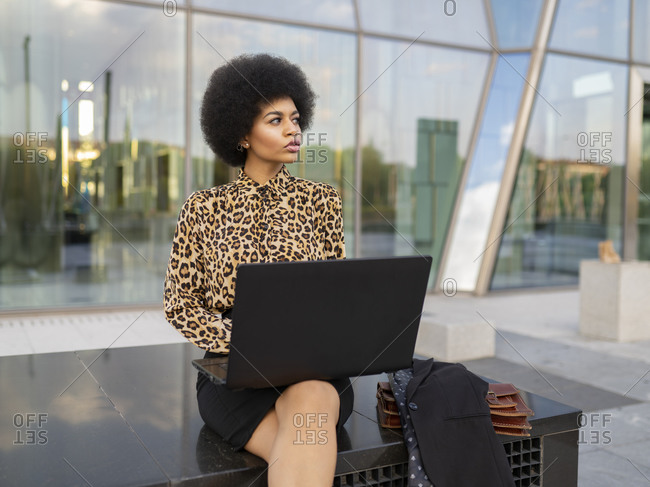 Busy African American female manager sitting on bench with computer and cup of drink and typing text while working remotely near glass building