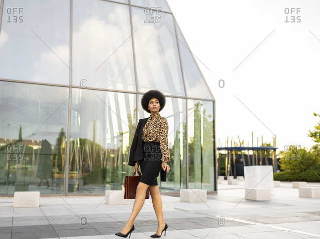Full body of unemotional thoughtful stylish African American female employee with afro hair and briefcase walking near glass walled building