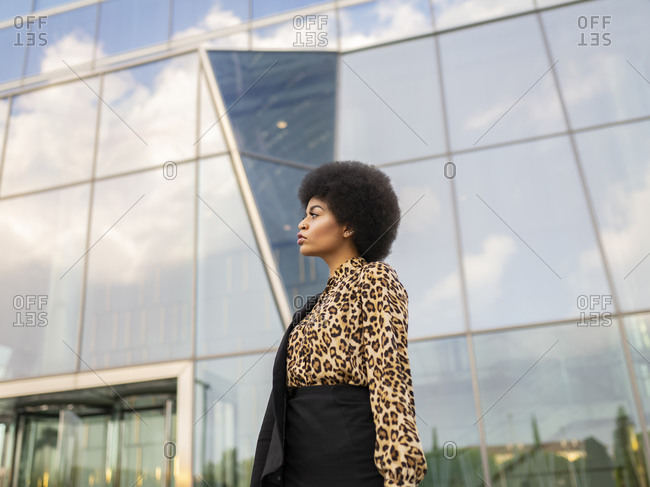 Confident African American female in formal wear standing near modern office building in downtown