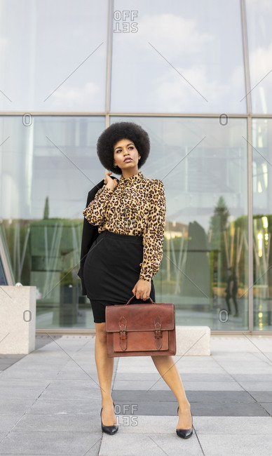 Full body of unemotional thoughtful stylish African American female employee with afro hair and briefcase holding jacket in hands standing near glass walled building