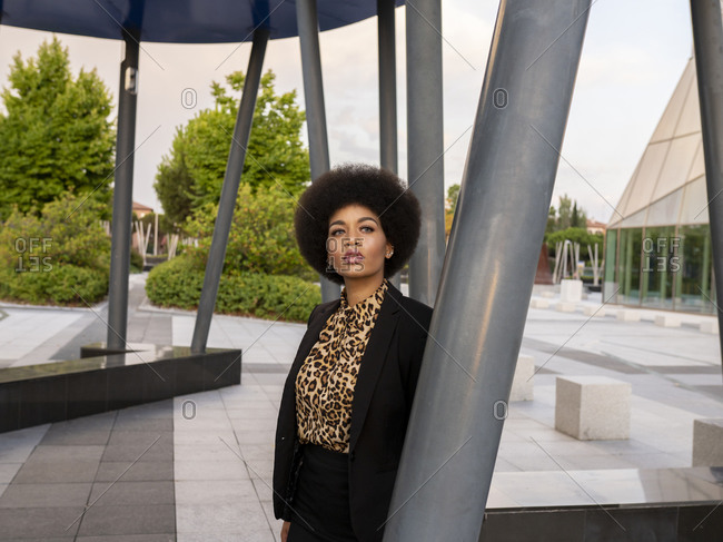 Dreamy African American female in elegant outfit standing near metal construction and thoughtfully looking away
