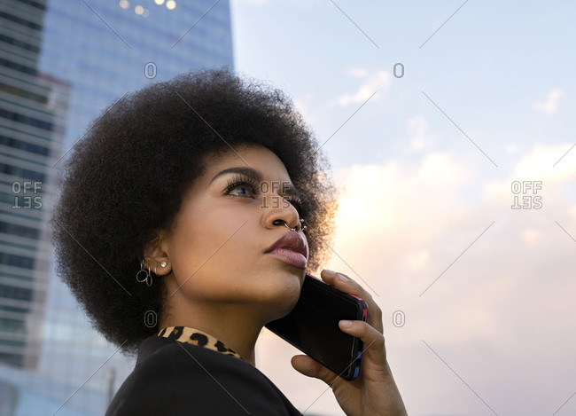 From below side view of African American female with curly hair standing on street and calling on smartphone