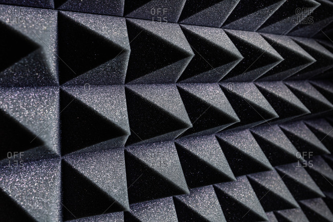 Textured background of wall with black geometric soundproof foam with pyramid shaped pattern in recording studio