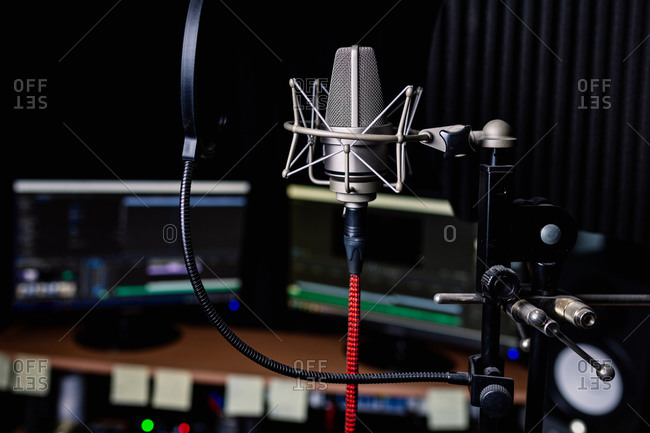 Contemporary metal microphone with wire placed in dark music recording studio on blurred background of computer monitors