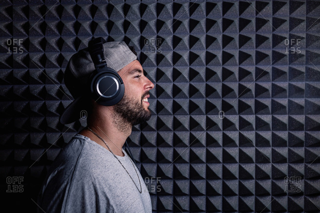 Side view of stylish male singer wearing headphones standing in recording studio on background of soundproof acoustic panel and looking at camera