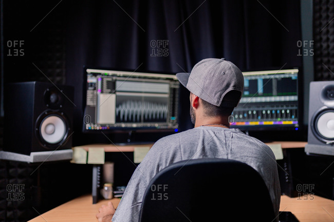 Back view of unrecognizable male musician sitting at table with monitors and stereo speakers while recording audio in studio