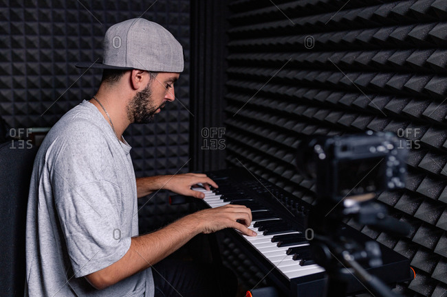Side view of skilled male musician playing electric piano and recording video on camera in acoustic room with soundproof foam walls