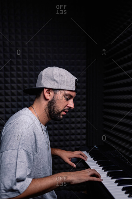 Side view of skilled male musician playing electric piano in acoustic room with soundproof foam walls