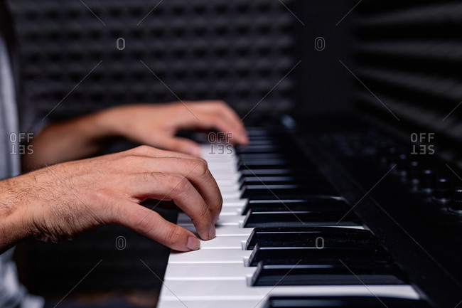 Cropped unrecognizable skilled male musician playing electric piano in acoustic room with soundproof foam walls