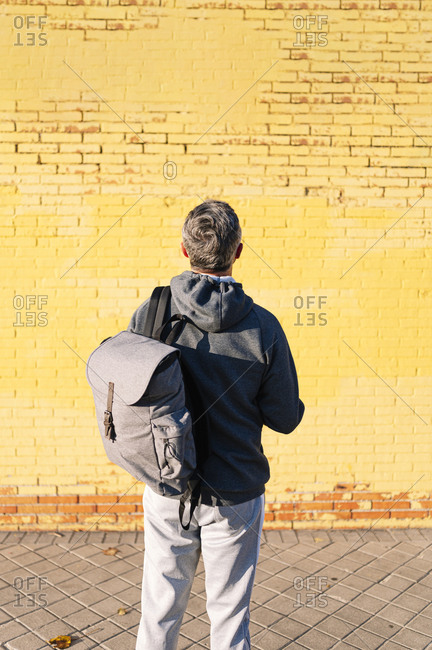 Retired senior man athlete looking at a yellow wall with sportswear and backpack