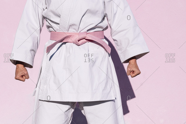 Cropped unrecognizable determined mature woman in pink head cover and belt fighting karate in cancer battle concept in the street on pink wall