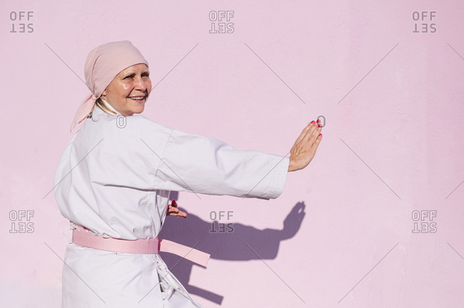 Side view of determined happy mature woman in pink head cover and belt fighting karate in cancer battle concept in the street on pink wall looking at camera