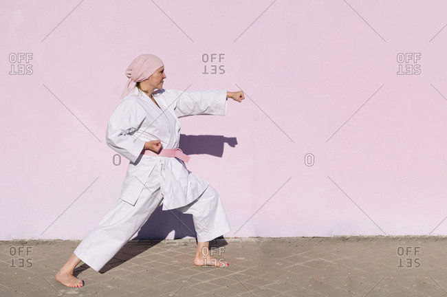Side view of determined mature woman in pink head cover and belt fighting karate in cancer battle concept in the street on pink wall looking away