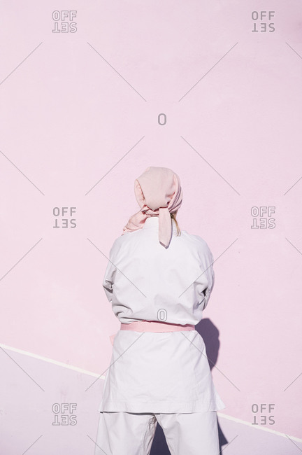 Back view of unrecognizable determined mature woman in pink head cover and belt fighting karate in cancer battle concept in the street on pink wall