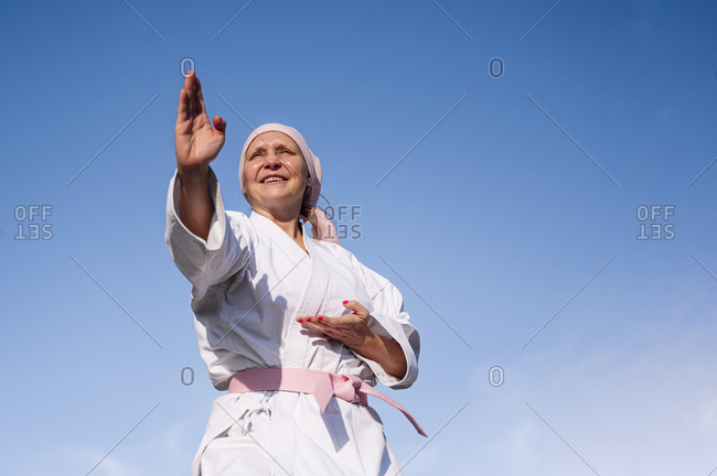 From below determined mature woman in pink head cover and belt fighting karate in cancer battle concept standing on blue sky background looking away