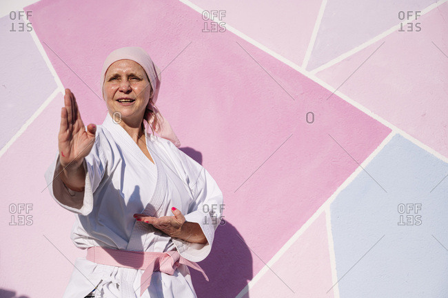 Determined mature woman in pink head cover and belt fighting karate in cancer battle concept in the street on pink wall looking away