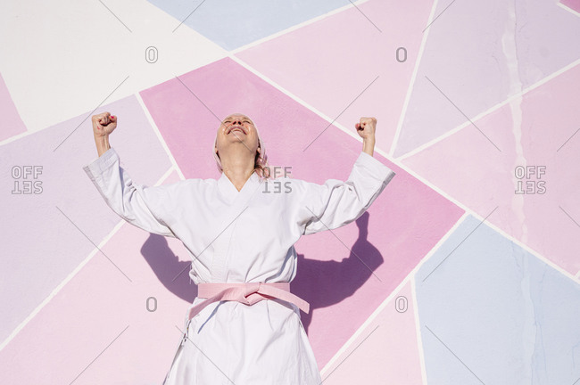 Determined mature woman in pink head cover and belt fighting karate in cancer battle concept doing victory gesture in the street on pink wall looking up