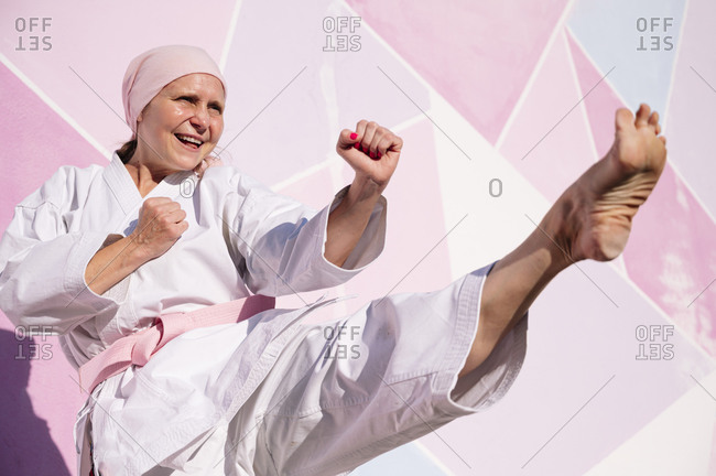 Determined cheerful mature barefooted woman in pink head cover and belt kicking fighting karate in cancer battle concept in the street on pink wall looking away